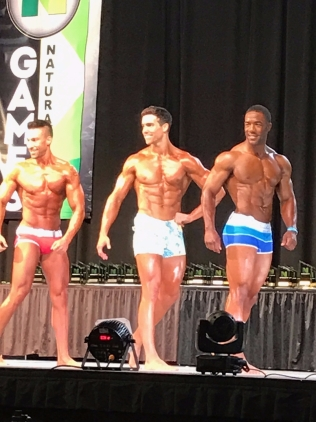 Derek Tresize (center) competing in Men's Physique.